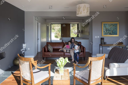 Interior View Of Lounge With Family On Sofa. Upside Down House, Balcombe,  ...